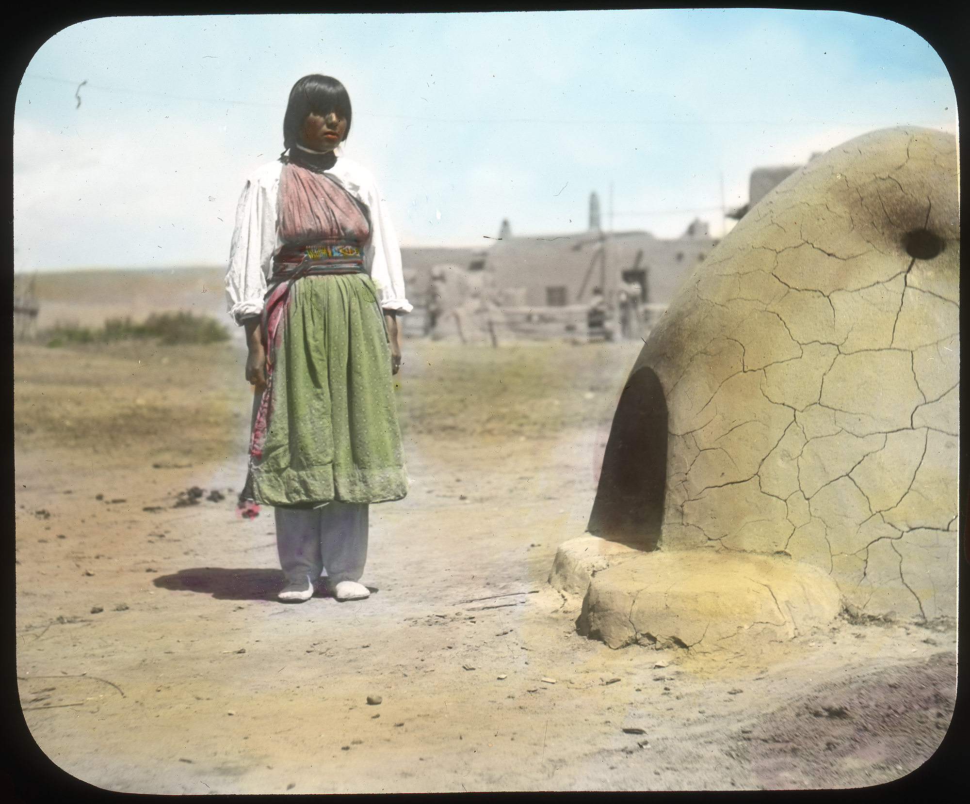 A lantern slide of a Native American woman standing next to a clay oven.