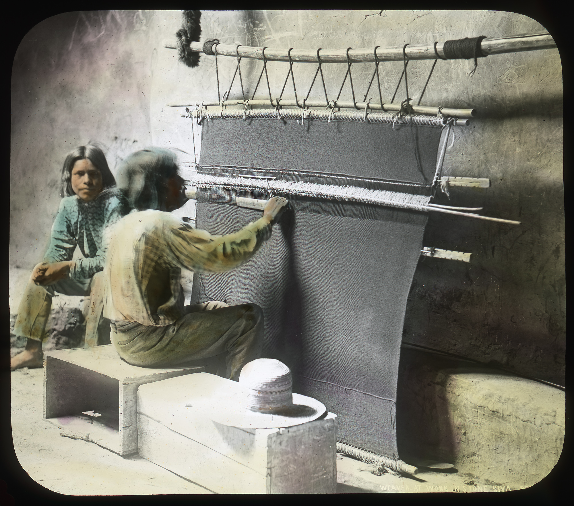 A Native American man weaves a rug on a loom.