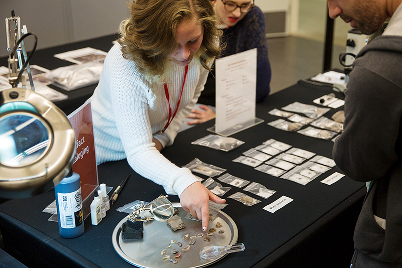 A museum intern shows a guest arrowheads.