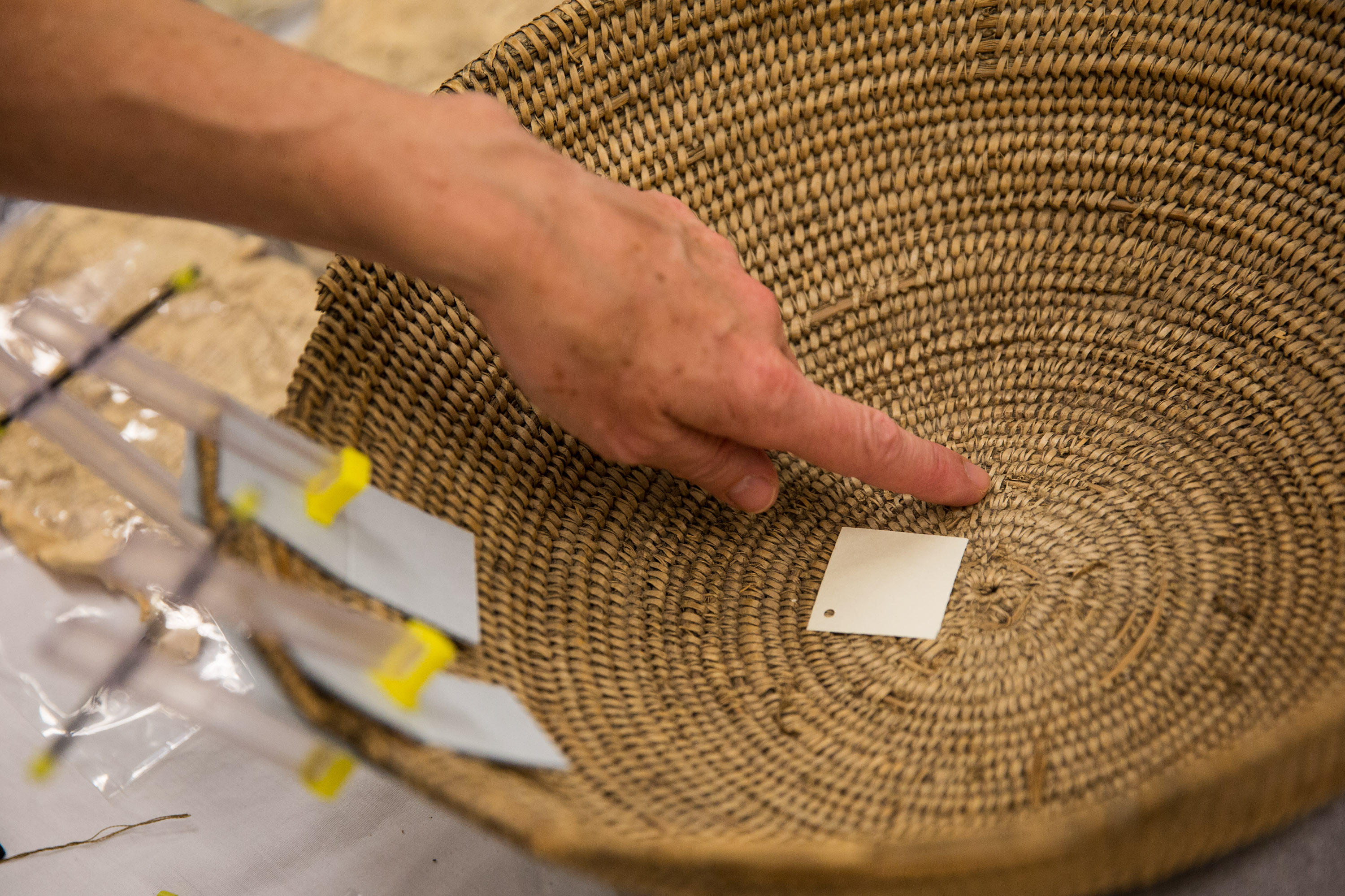 Woman examining damaged basket and preparing to restore it.