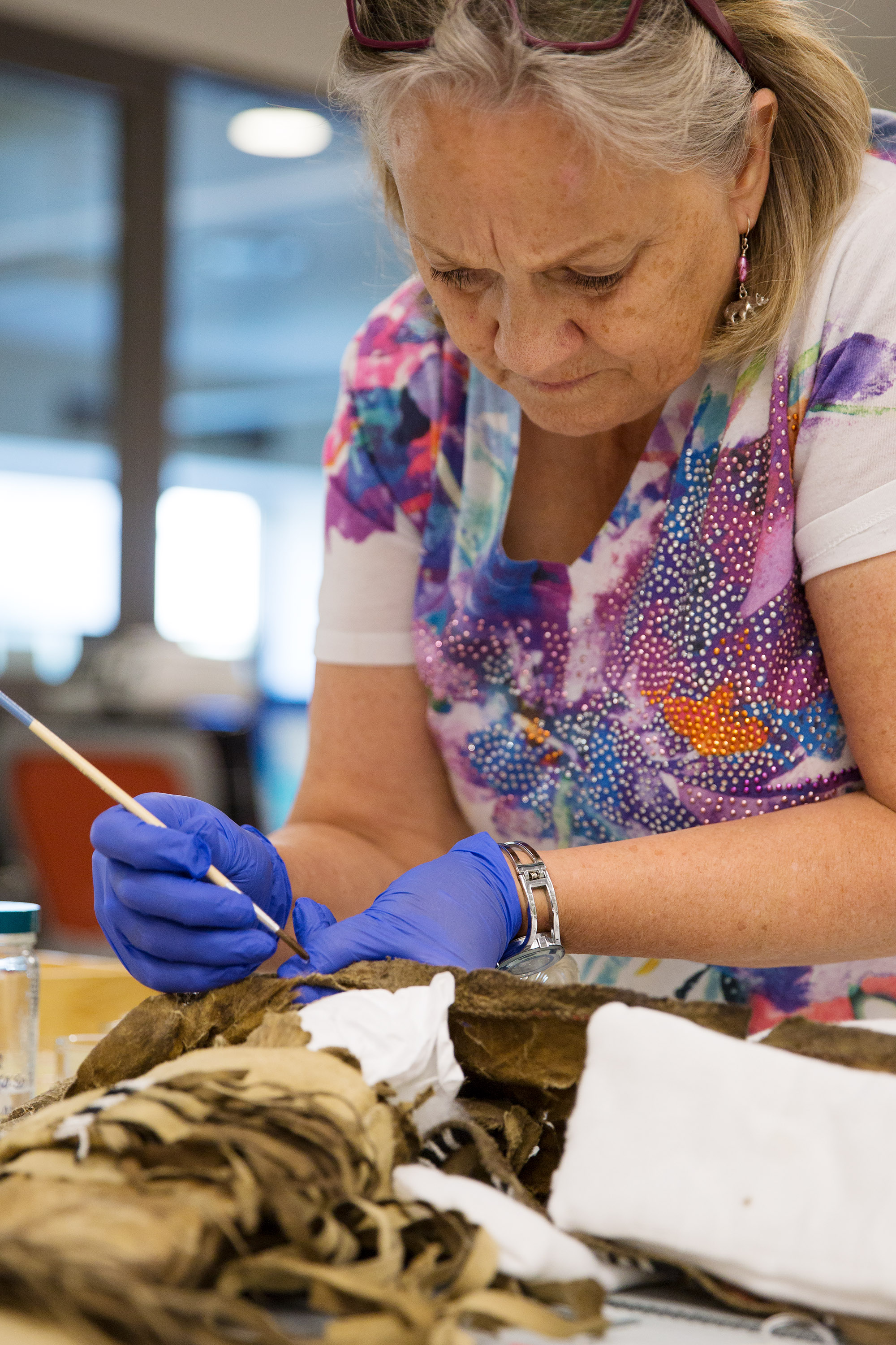 Anthropology Collections Manager, works to restore damage done by light and insects to an Otter-skin quiver collected by explorer John Wesley Powell.
