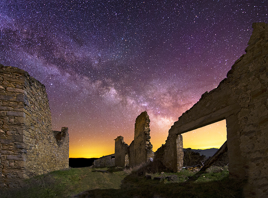 An unspecified ancient ruin is silhouetted by a star-filled night sky.