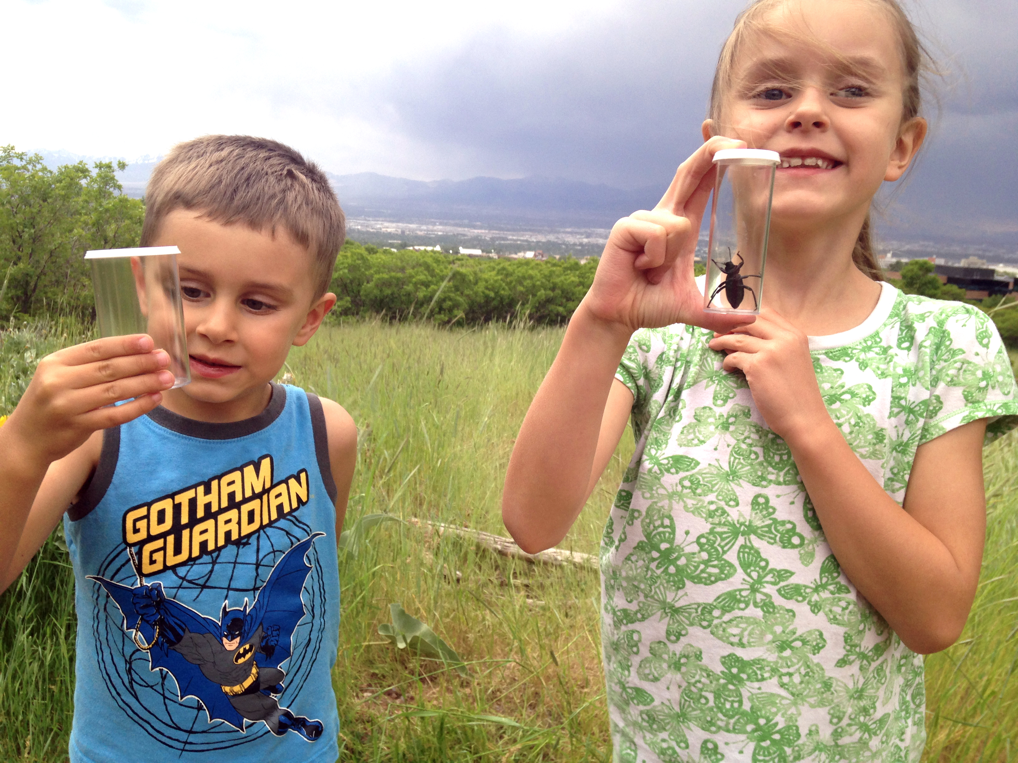 Kids holding jars with bugs inside