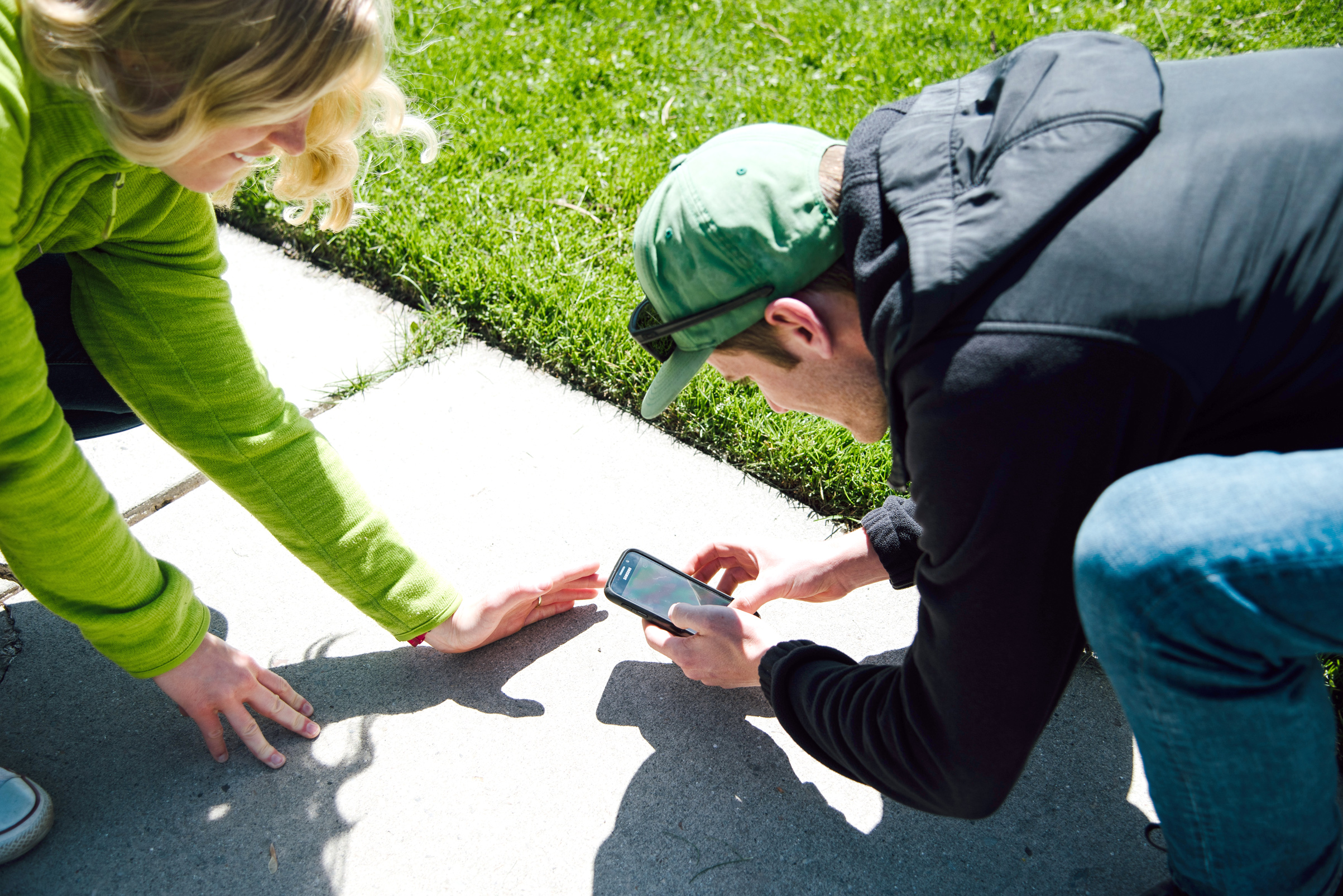 Man and woman crouched down on the sidewalk using cell phone to capture image of small bug.