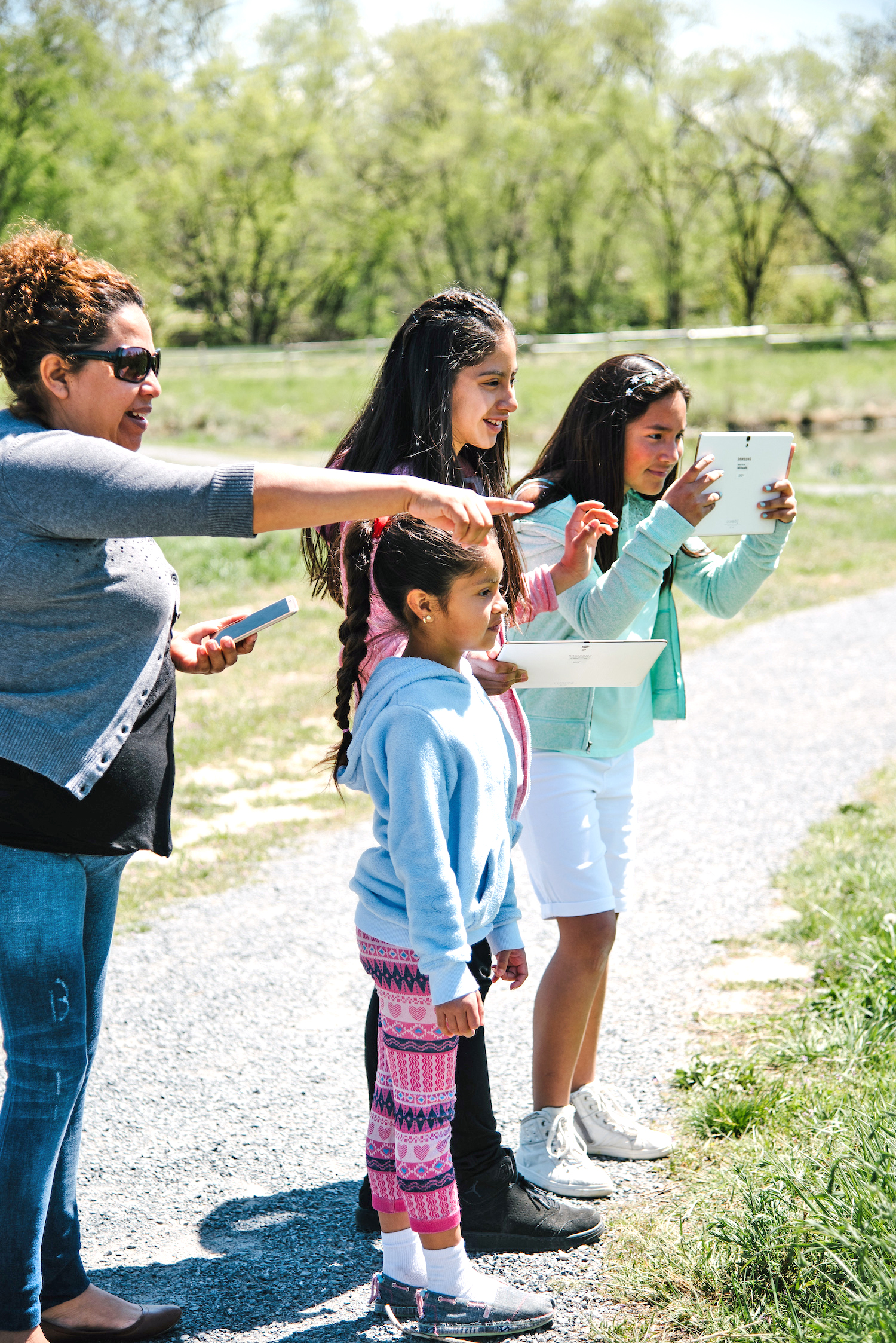 A mother and three girls taking photos of the wildlife at the Fife Wetland Preserve.