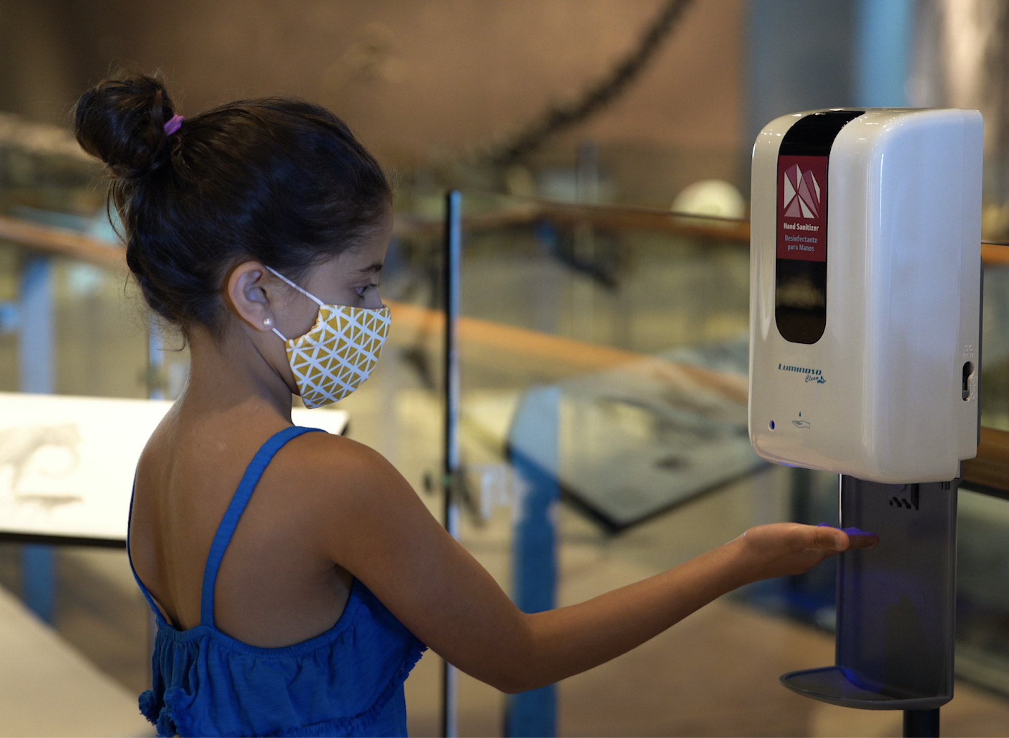 image of girl with mask putting on hand sanitizer