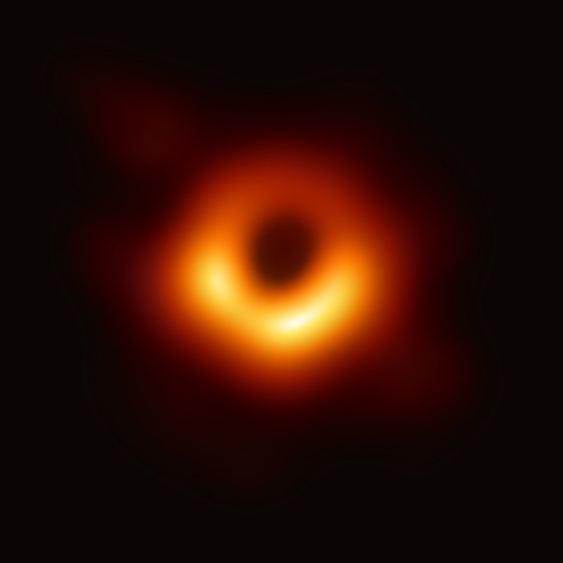 The first image of a black hole, an orange ring in space.