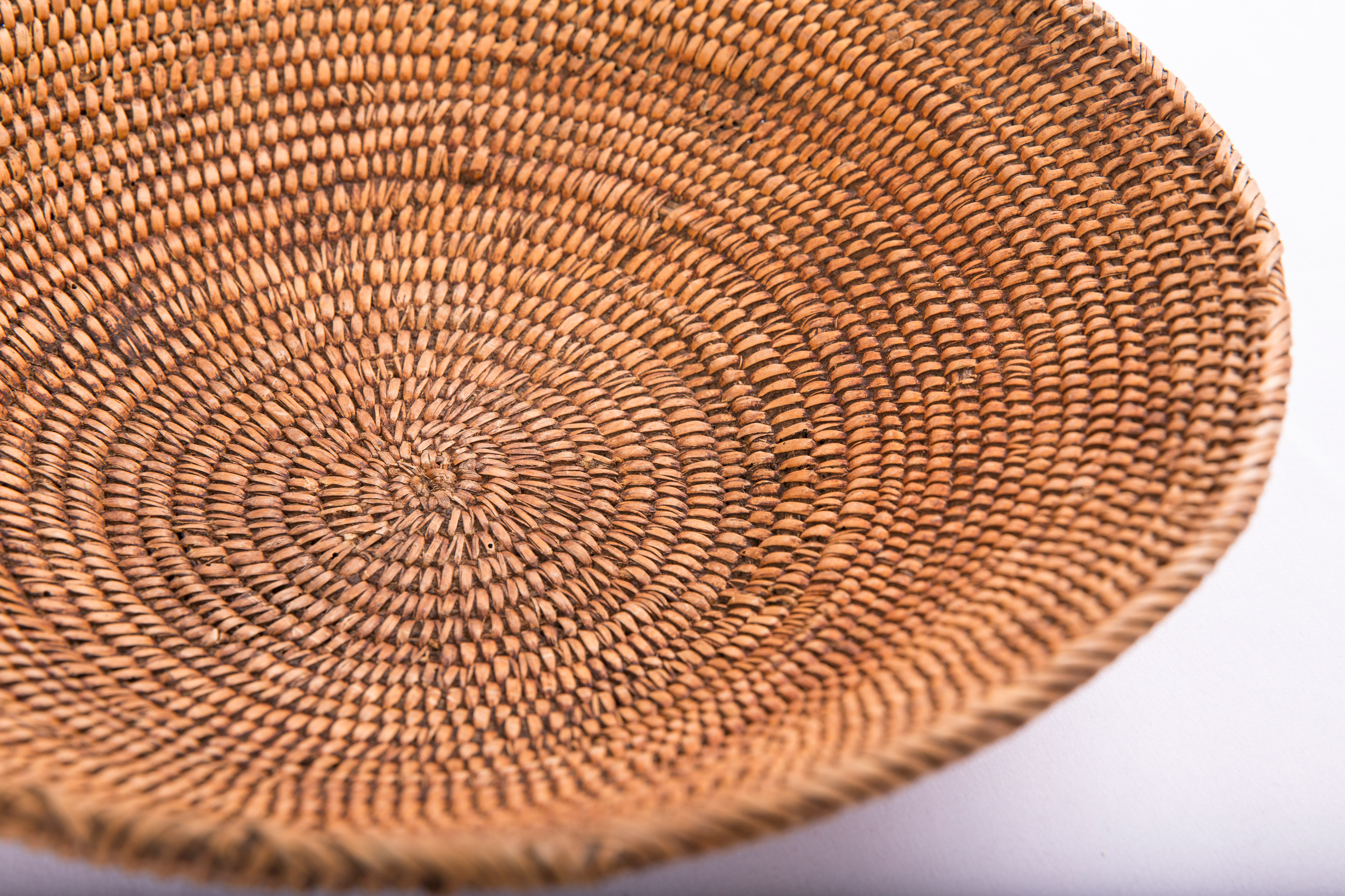 Shallow coiled Northern Ute basket with some burn marks.
