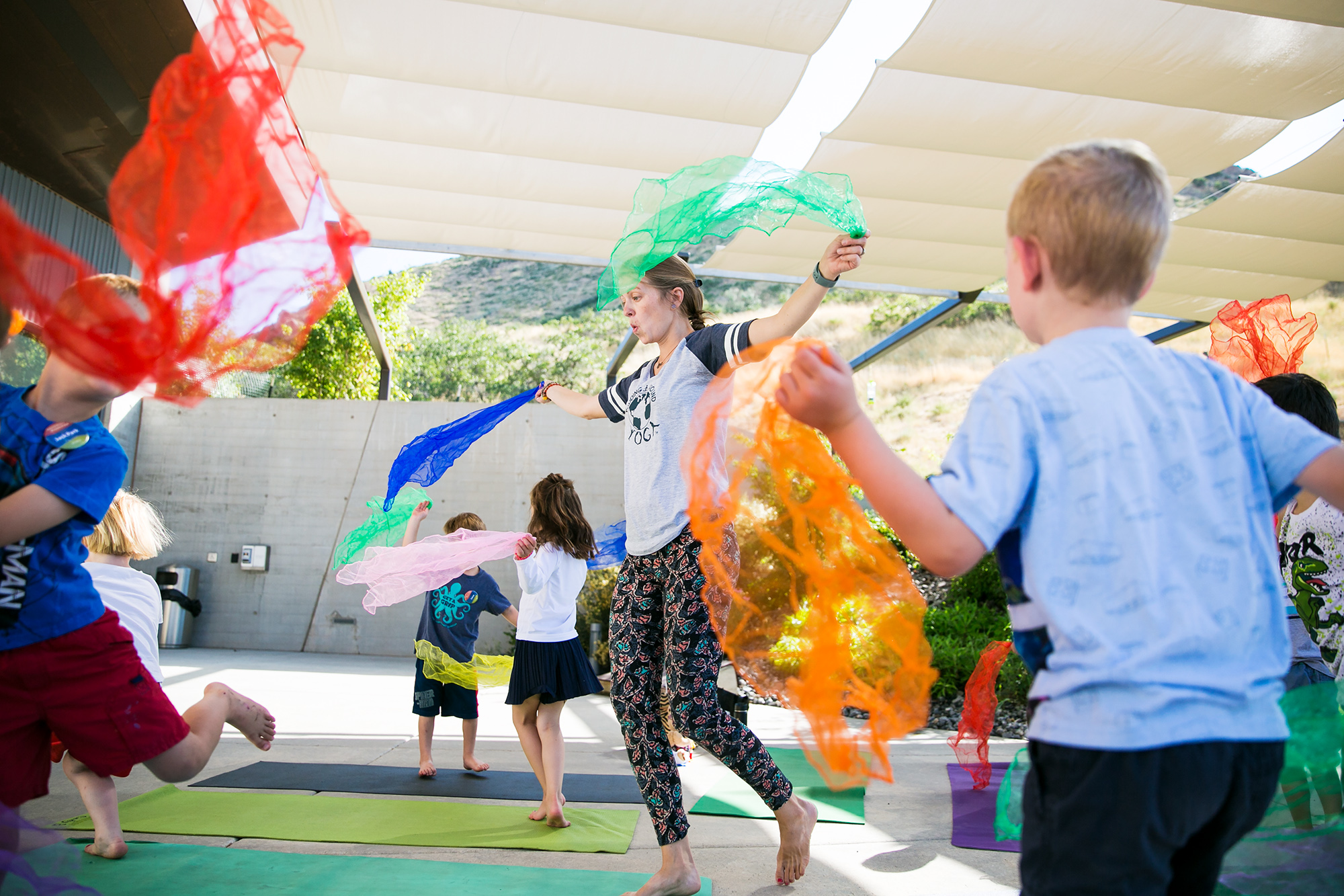 A yoga instructor leads children in improvised dance waving colorful scarves.