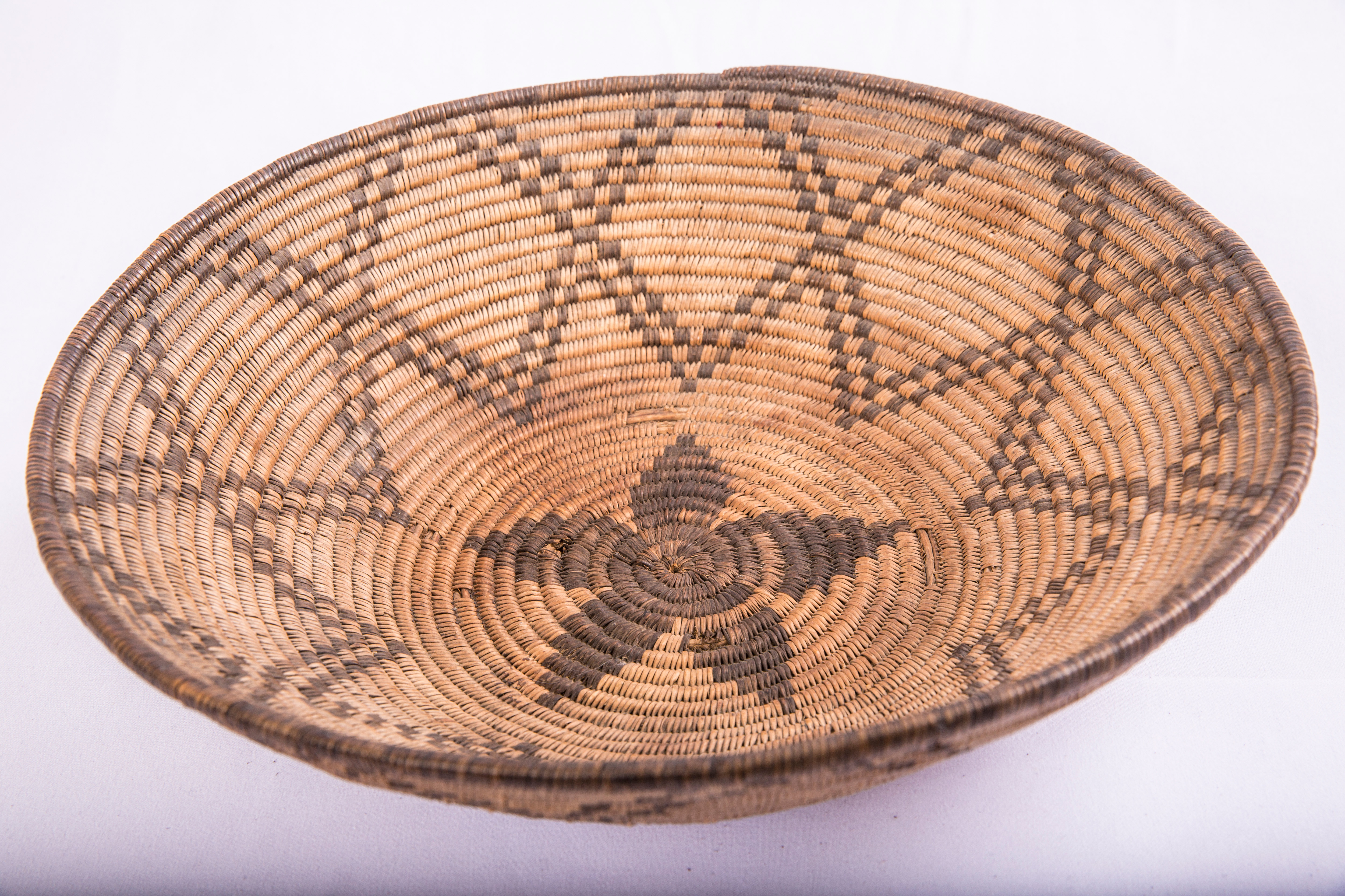 Cooking basket made of willow and black martynia. Star/flower motif with radiating petals and crossing double lattice pattern stitched in black.