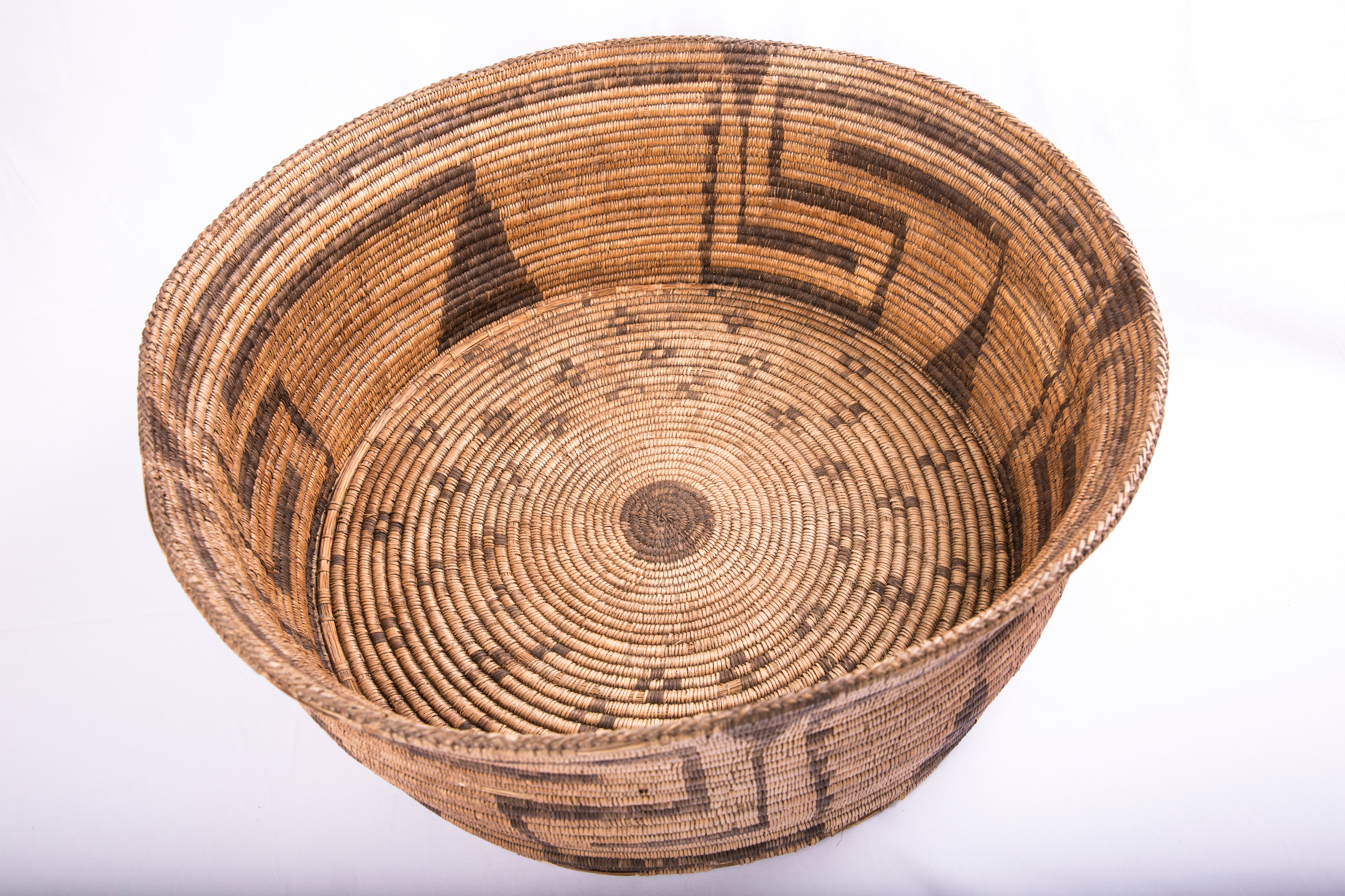 Flat bottomed basket with geometric pattern running along the sides