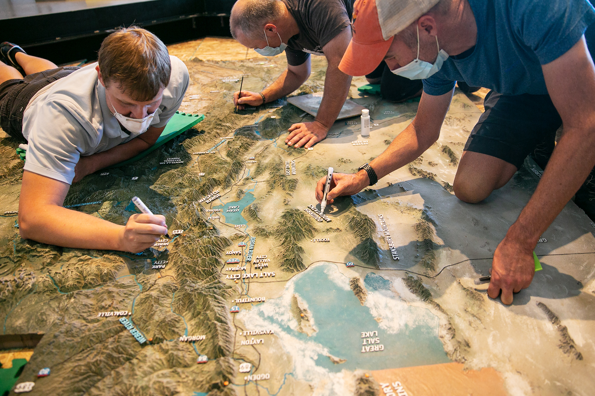 Team members from Creotrē add finishing touches to the new 3D map of Utah installed at NHMU.