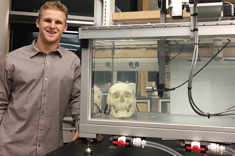 A scientist stands next to a glass case containing a human skull.