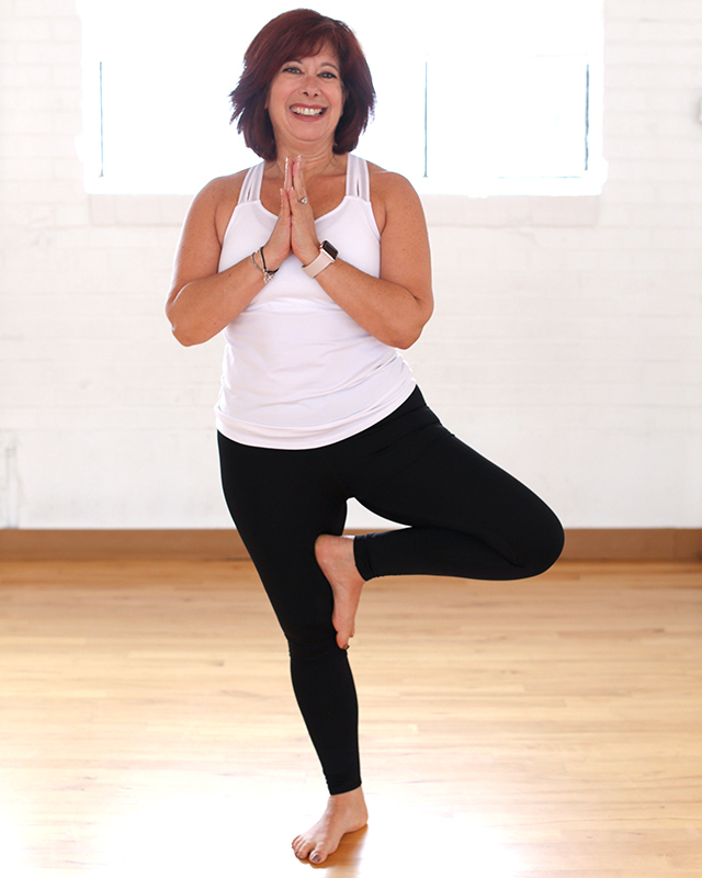 A yoga instructor stands in tree pose before a white brick wall.