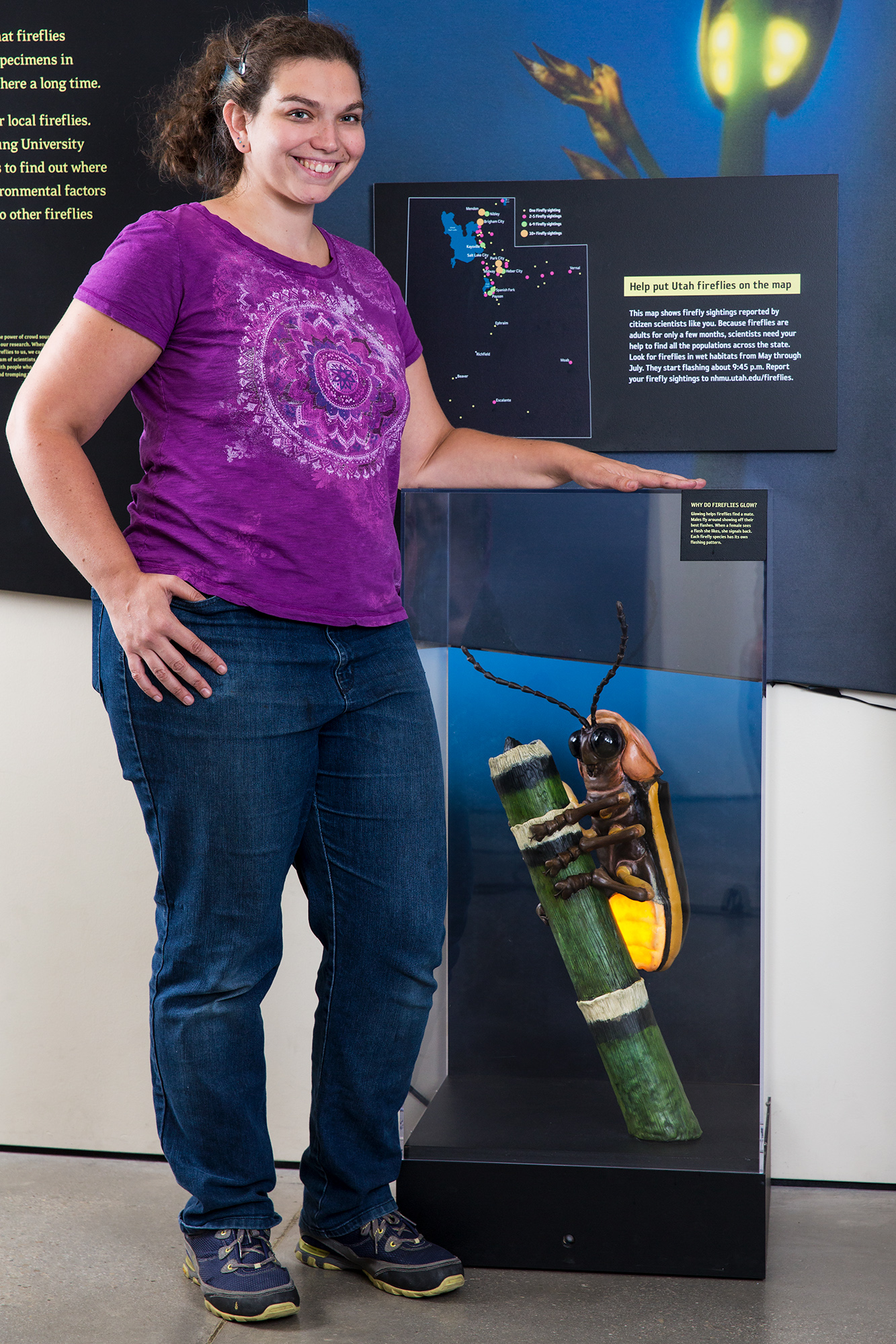Preparator Emily Szalay stands next to a firefly model she built at NHMU.
