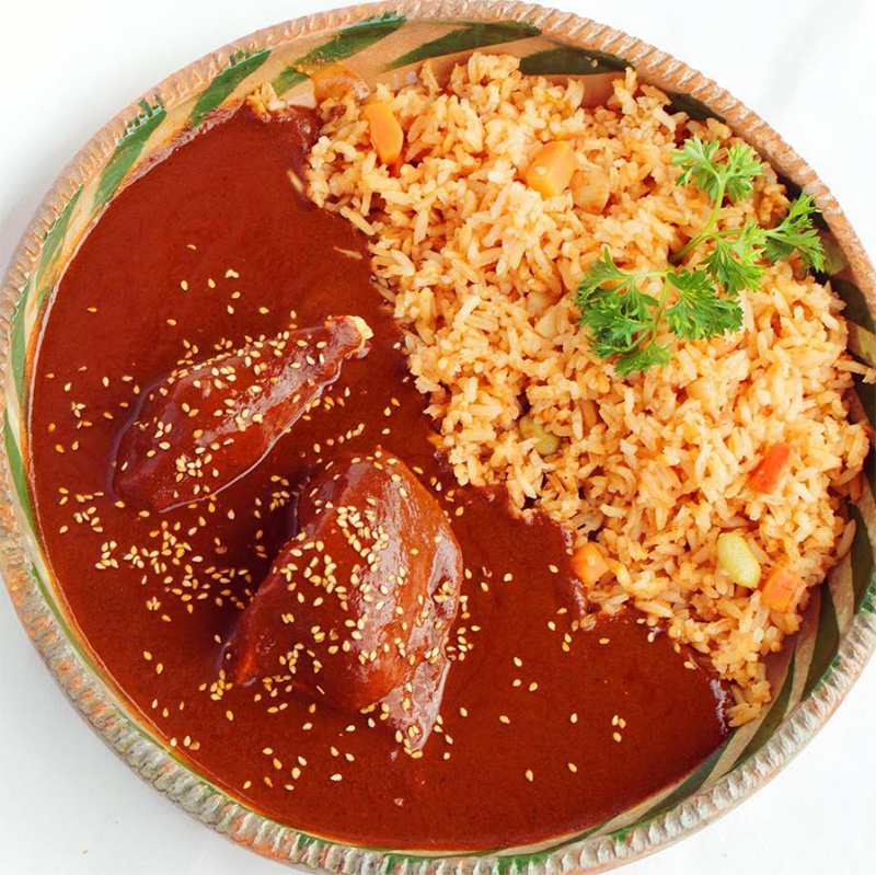 A plate of rice and chicken smothered in mole.