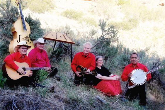 Band members sit in the grass wearing matching red shirts.
