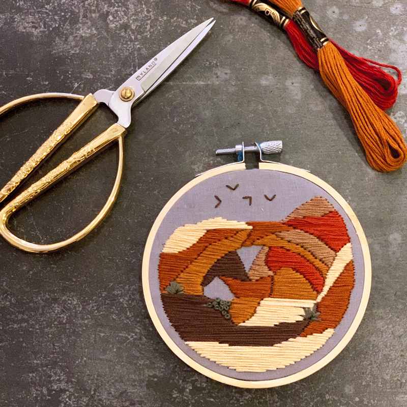 An embroidery of a red rock landscape.