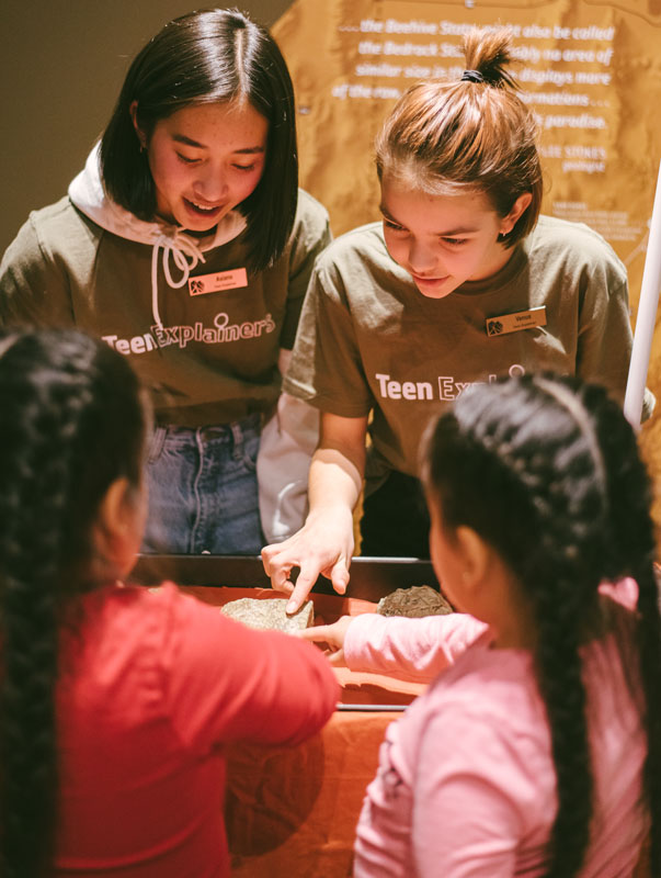 Teenager guides interact with museum guests.