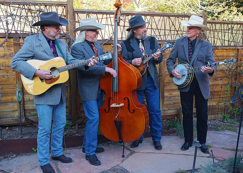 Group photo of the bluegrass band, The Grey Hounds, with instruments.