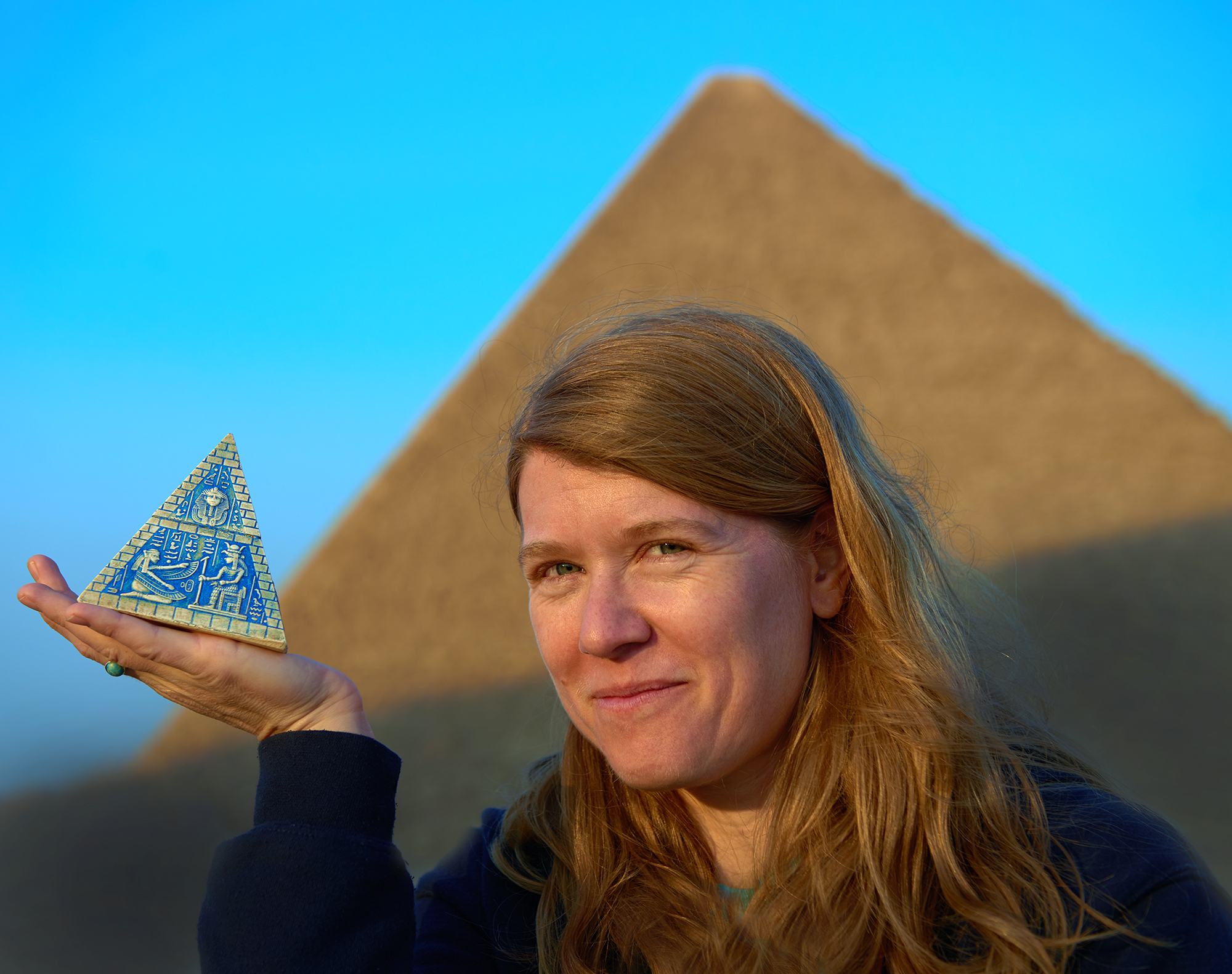 Photo of Sarah Parcak holding a pyramid in her hand with an ancient pyramid behind her.