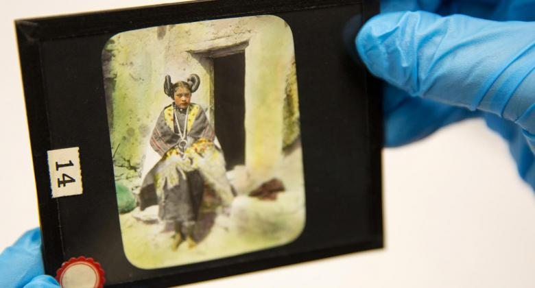 An anthropologist holds a lantern slide featuring a Hopi girl wearing traditional clothing.
