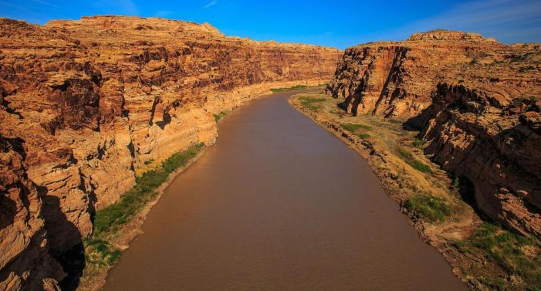 A view of the Colorado River in southeast Utah, with tall, rocky, red cliffs flanking the rust red river on either side. the