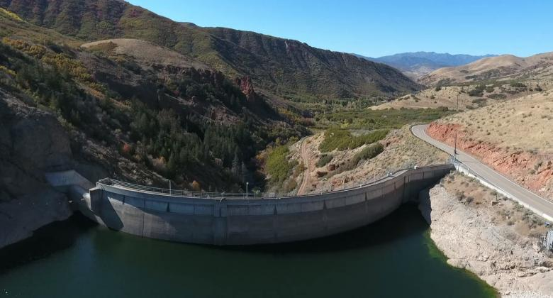 A view from behind the East Canyon Dam, showing the water held behind the curved human-made structure.