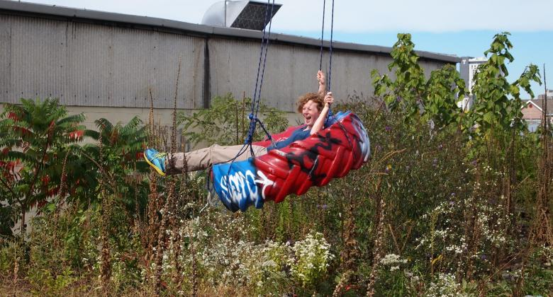 Writer Emma Marris on a giant tire swing above an abandoned rail line with flowers and other plants growing all around.