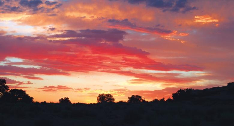 An inspiring desert sunset, showing blues, purples, oranges, and more.
