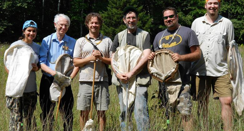 Image of researchers lined up for group photo in the field with insect nets--includes the author Jason Cryan.
