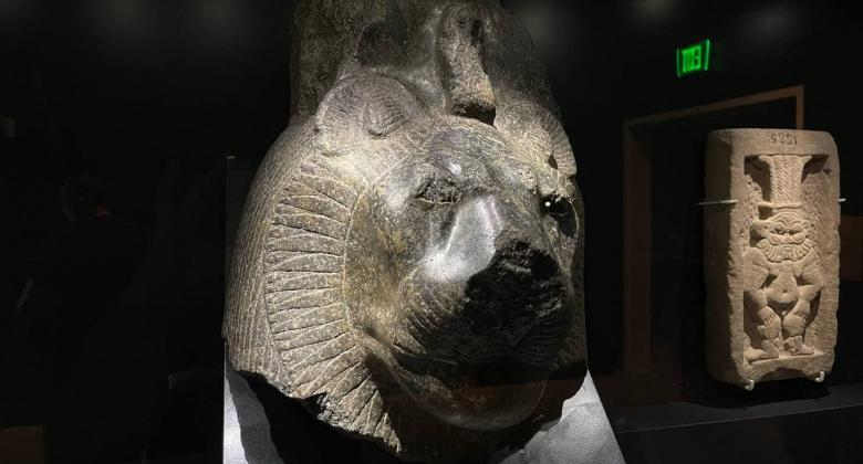 An image of a dark stone sculpture depicting the lion head of the goddess sekhmet.