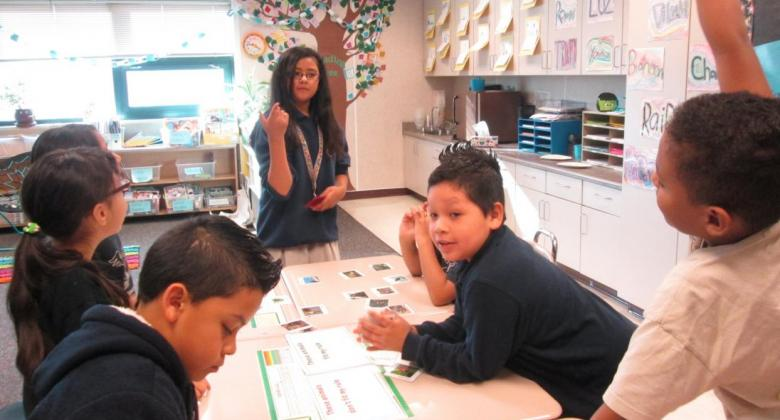 Young students teaching other students in a classroom, with one student raising their hand to answer a question.