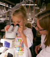 A girl peers into a microscope.
