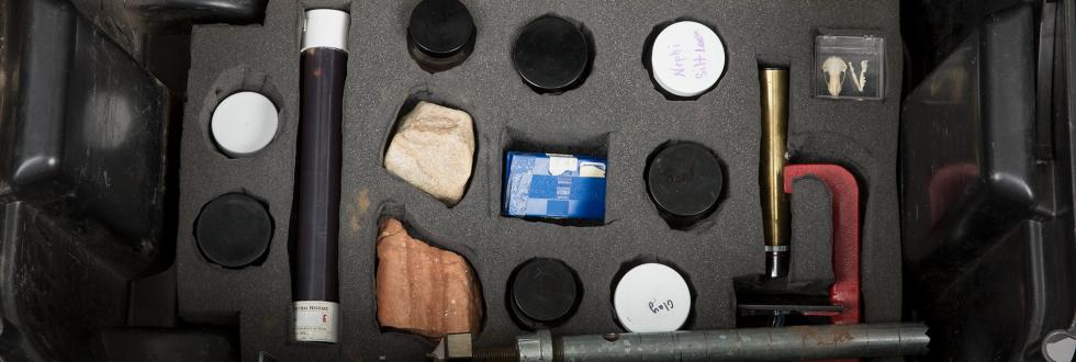 A selection of tools and rock samples in a black box.