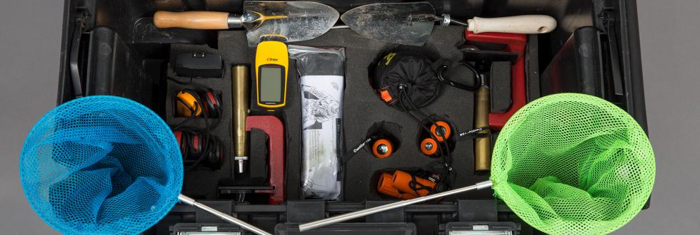 A selection of tools and insect nets in a black box.