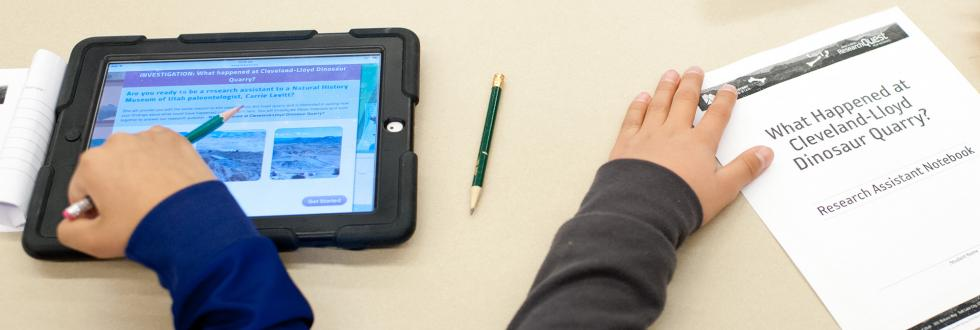 Children hold a tablet and a paper at a classroom table.