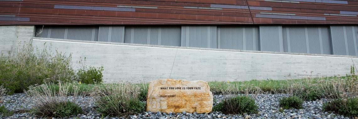 A rock inscribed with poetry outside a museum.