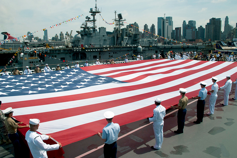 A large American flag is held by sailors and marines on the deck of a naval ship.